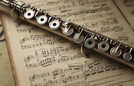 old silver flute on vintage music notes