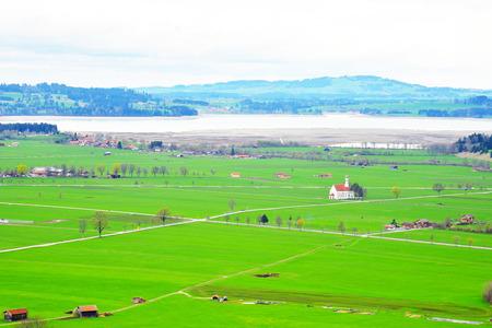 A beautiful view of green field, church from Neuschwanstein lookout Stock Photo