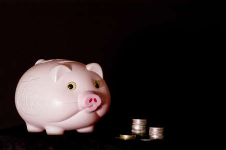 a pink piggy bank and coins Stock Photo