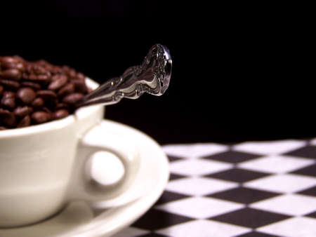 Color photo of a cup full of dark brown coffee beans with a silver spoon sticking out from it.  The focus is on the tip of the spoon. photo