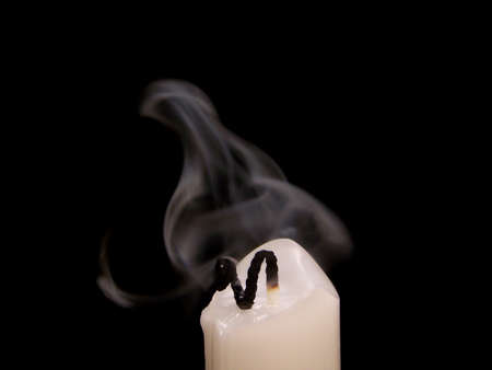 taper: Small, white taper candle with a curling black wick that has been extinguished.  This wisps of smoke are floating just above the candle.  Black background.