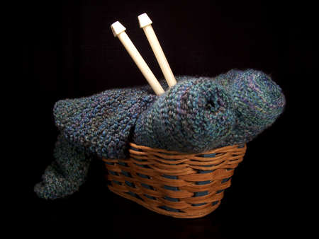 Beautiful color photo of a basket of knitting supplies with yarn, knitting needles, and a small knitted piece. Stock Photo - 1492007