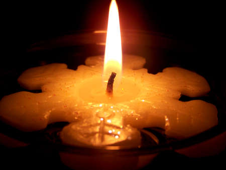 Burning snowflake candle floating in water on a black background. Stock Photo