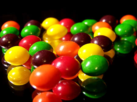 mirror image: This is an image of colorful, fruity candies reflecting in a mirror on a black background. Stock Photo