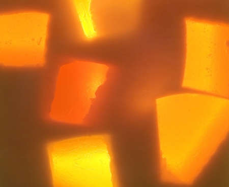 glycerin soap: Full frame photograph of yellow and orange handmade glycerin soap with a light shining through it giving it an abstract glow. Stock Photo
