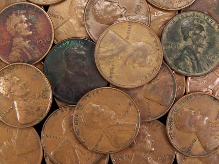 tarnish: Full frame photo of several vintage United States wheat pennies with the head side facing up showing dates.  These coins have a lot of texture and some discoloring from age. Stock Photo