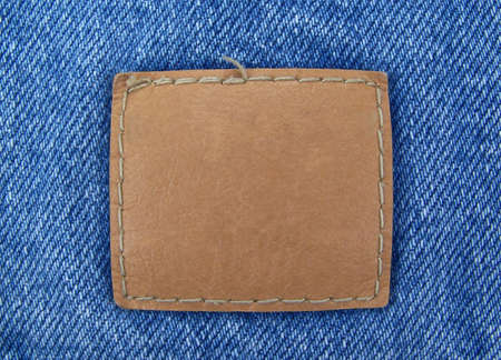 sew tags: A blank, brown leather tag sewn onto blue denim.