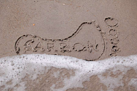 A footprint drawn in the sand with the word  Stock Photo