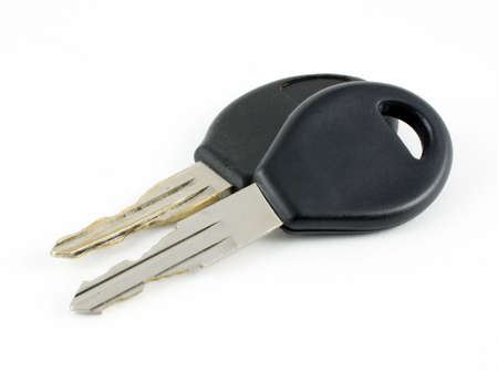 A close-up photograph of a new car key resting against an old, very worn car key on a white background  Stock Photo - 18049911