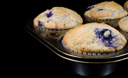 Close-up photograph of fresh baked, homemade blueberry muffins in a well used muffin pan on a black background. Stock Photo - 18467343