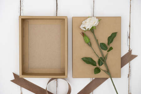 Opened cardboard box on a white wooden table Stock Photo