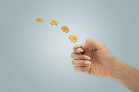 Hand is flipping a coin isolated on blue background.