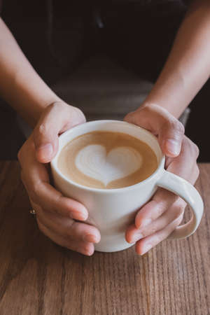 Hand holding a cup of coffee with heart foam milk.