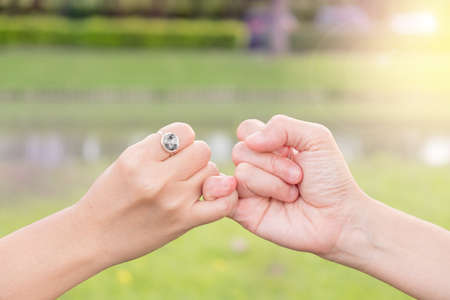 Couples use their little fingers together in the garden.