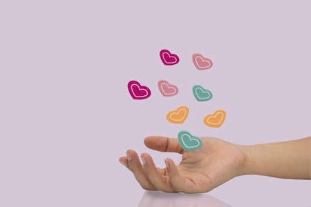 Many color wooden heart ball on woman hand isolated on purple background. 免版税图像