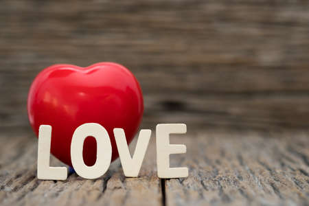 Image-One Heart and love word on wooden background. Copy space Valentines day concept.