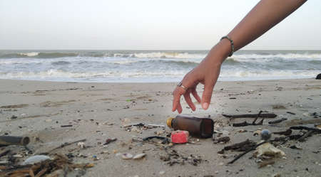 Hand is keeping Garbage washes up on Songkhla beach.
