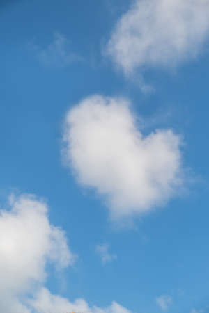 blue sky with hearts shape in clouds.