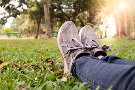 Woman feet in sneaker on green grass in the park at sunset. 免版税图像