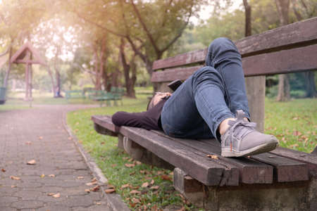 A woman is sleeping on the bench in the park.