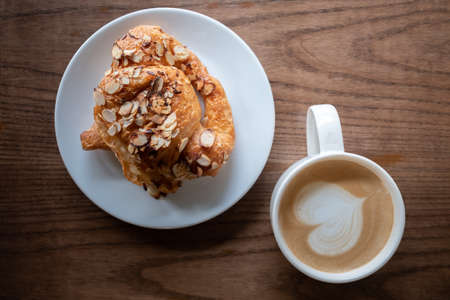 A cup of coffee with almond croissant in the morning light.