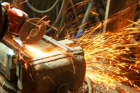 Worker sawing metal with electrical saw, grinder