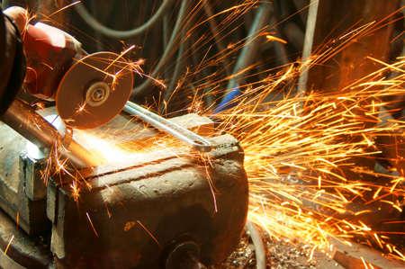 die: Worker sawing metal with electrical saw, grinder