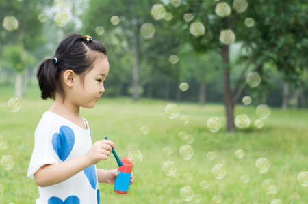 little girl with wreath from flowers blows soap bubbles photo