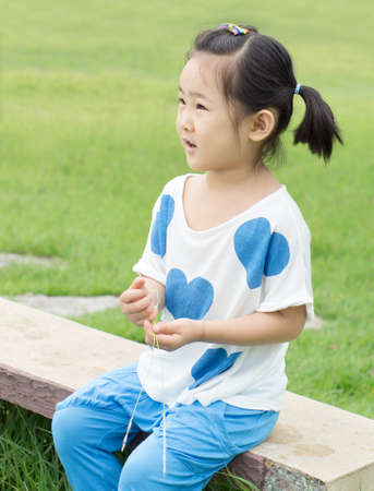 Happy little girl sitting on a park bench. Stock Photo