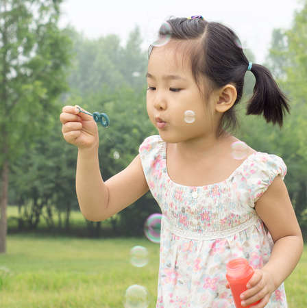 The little girl playing blowing bubbles game. photo