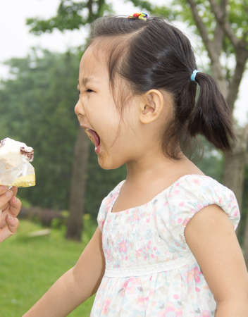 beautiful Asian little girl eating an ice cream and about to take a great big bite photo