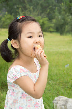 beautiful Asian little girl eating an ice cream and about to take a great big bite