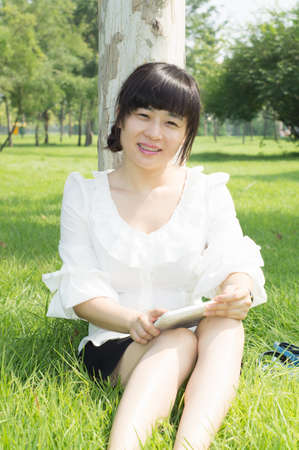 girl using tablet pc on the grass Stock Photo - 15000759