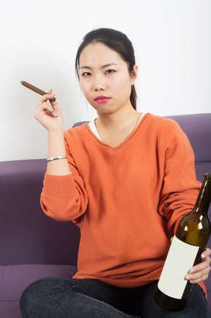 cigar smoking woman: Girl smoking a cigar holding the bottle Stock Photo