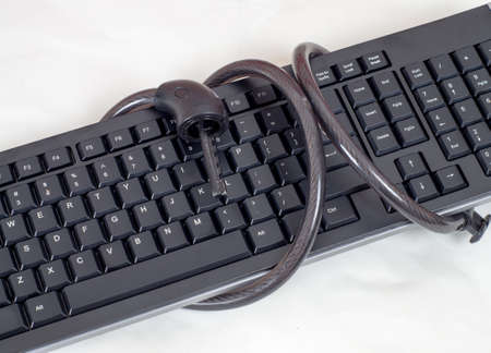 locked chain on computer keyboard as symbol for danger in internet photo