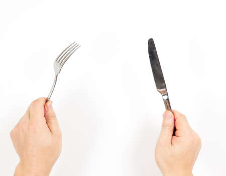 Knife and fork in hands isolated on white background Stock Photo