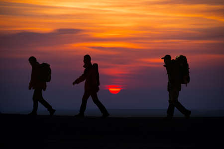The three hikers walk trip, in the top of the sunrise. Stock Photo
