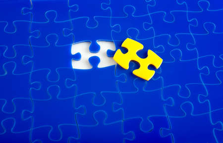 supplemental: Jigsaw Puzzle with the missing piece, yellow supplemental, shallow depth of field Stock Photo
