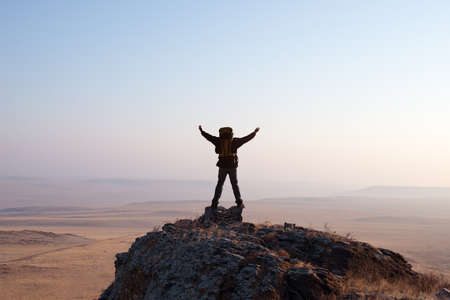 hiker enjoying sunrise from top of a mountain