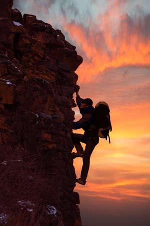 Man climbing on the rock on sunset background Stock Photo