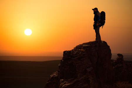 Hiker with backpack top of a mountain and enjoying valley view during sunrise