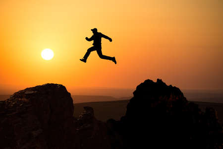 silhouette of a man jumping off a cliff in the direction of the bright sun photo