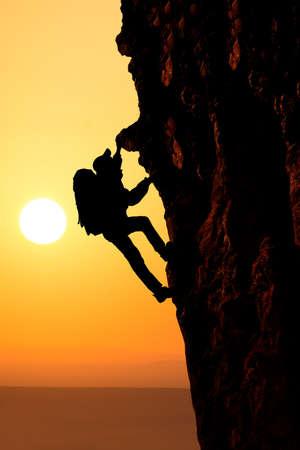 man climbing: Man climbing on the rock on sunset background Stock Photo