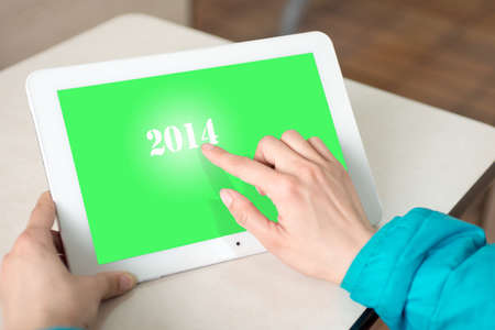 Girl using tablet. Click on the touch screen close-up hands  photo
