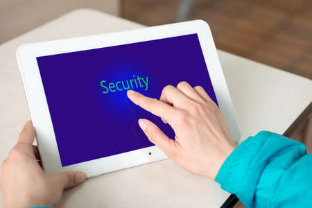Hand pushing security button on digital  of tablet PC photo
