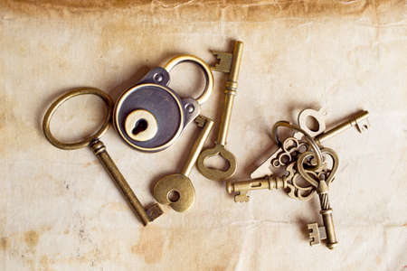 Retro copper keys and padlock on vintage paper background photo