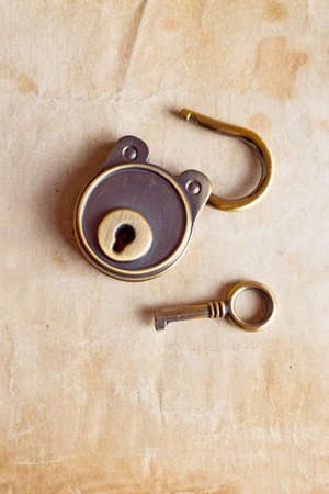 Retro copper keys and padlock isolated on the old paper background photo