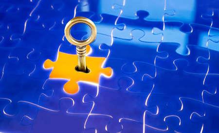 Key and keyhole close-up on yellow puzzle photo