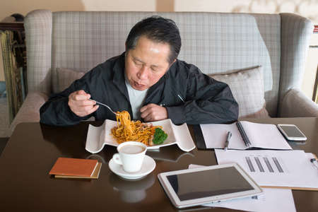 Male Customer Enjoying noodles And Coffee In Cafe photo