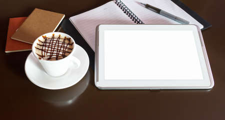 Close-up of a blank screen tablet computer, coffee cup in one side  photo